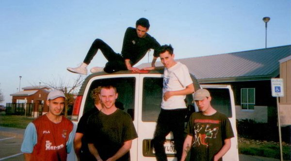 A group of young white men are pictured on and around a van