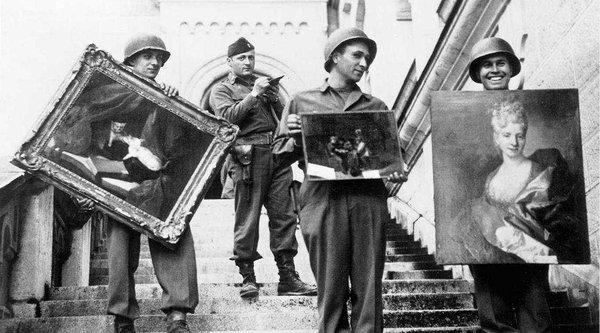 A black and white photograph showing men in army uniforms holding paintings