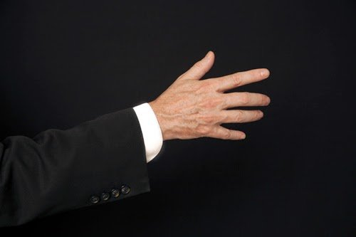 A man's hand and forearm against a black bakground