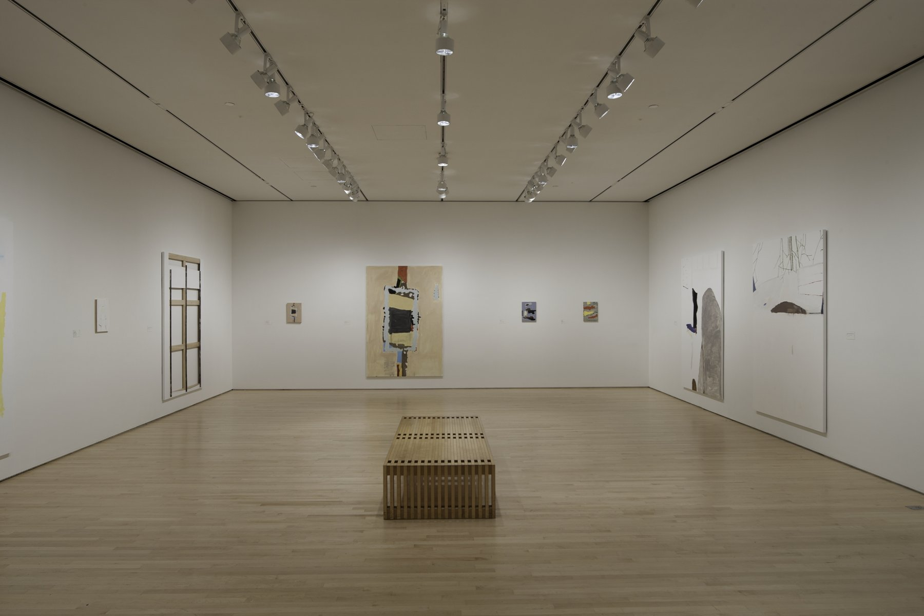 1.)	A white room with a bench in the middle of the room. The white walls have Richard Aldrich's work on them.