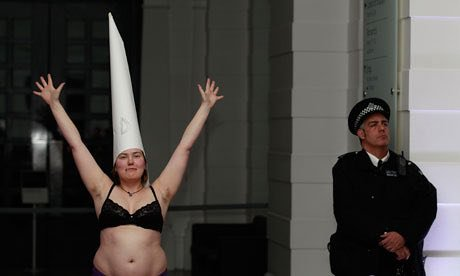 A Caucasian woman in a black bra wears a white dunce's cap and raises her arms