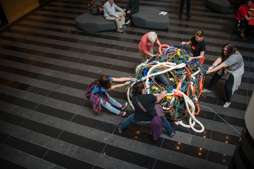 A group of people try pull at chords and ropes coming out of a massive tangle