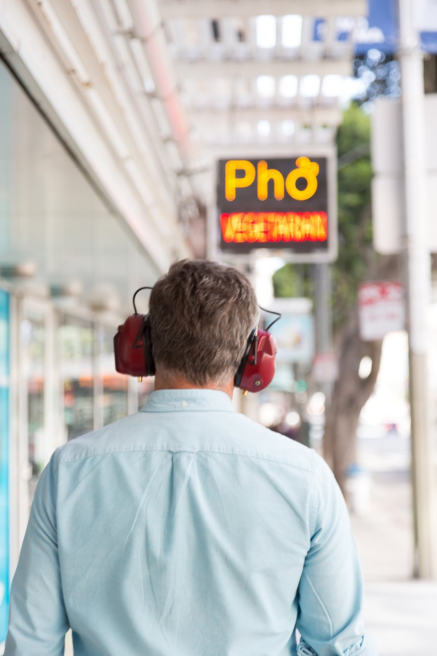 "A man wearing red headphones is seen from behind walking on a street toward a sign saying ""Pho"", Kubisch Soundtracks"