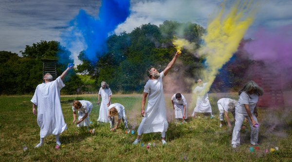 A group of adults wearing white togas fling colored powder into the air while standing in a field on a sunny day