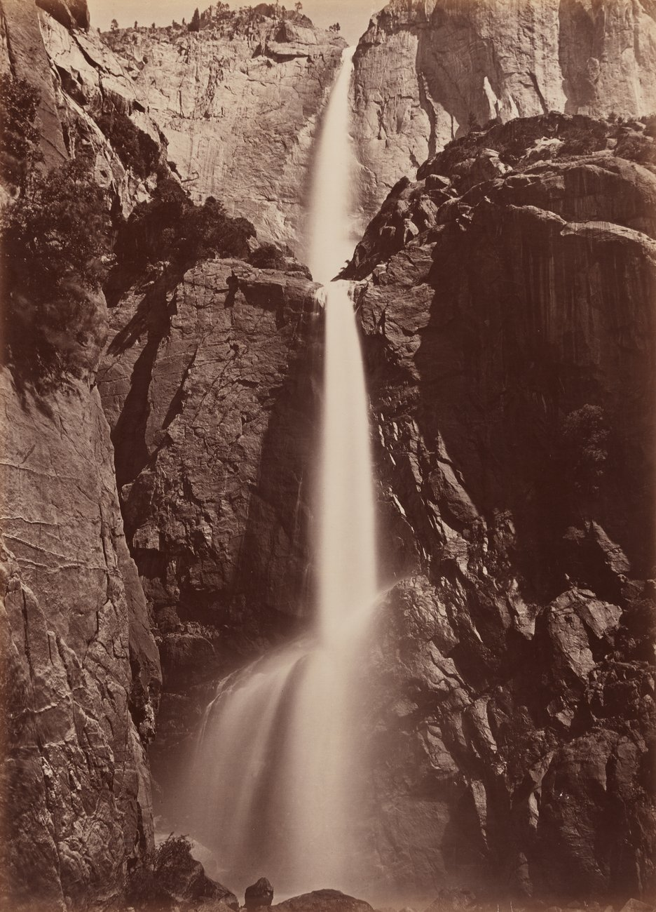 Sepia-toned black and white photograph of a tall cascading waterfall seen from below