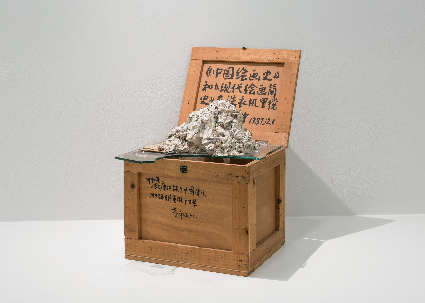 wooden box containing glass plane and crumpled newspaper