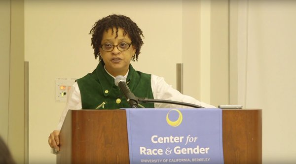 An African American woman wearing glasses speaks at a podium