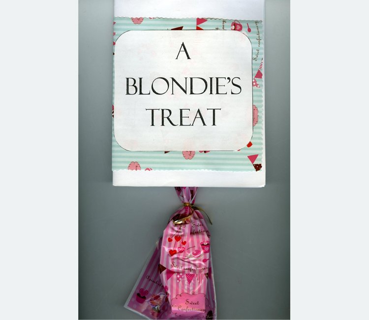 """A Blondie's Treat"" appear in black letters on a white label over wrapping paper with a pink candy bag hanging below"