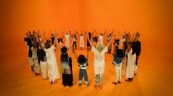 A group of people stand in a circle with arms upraised against an orange background, Holman