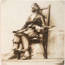 A sepia toned photograph of a woman strapped to an electric chair, Howard