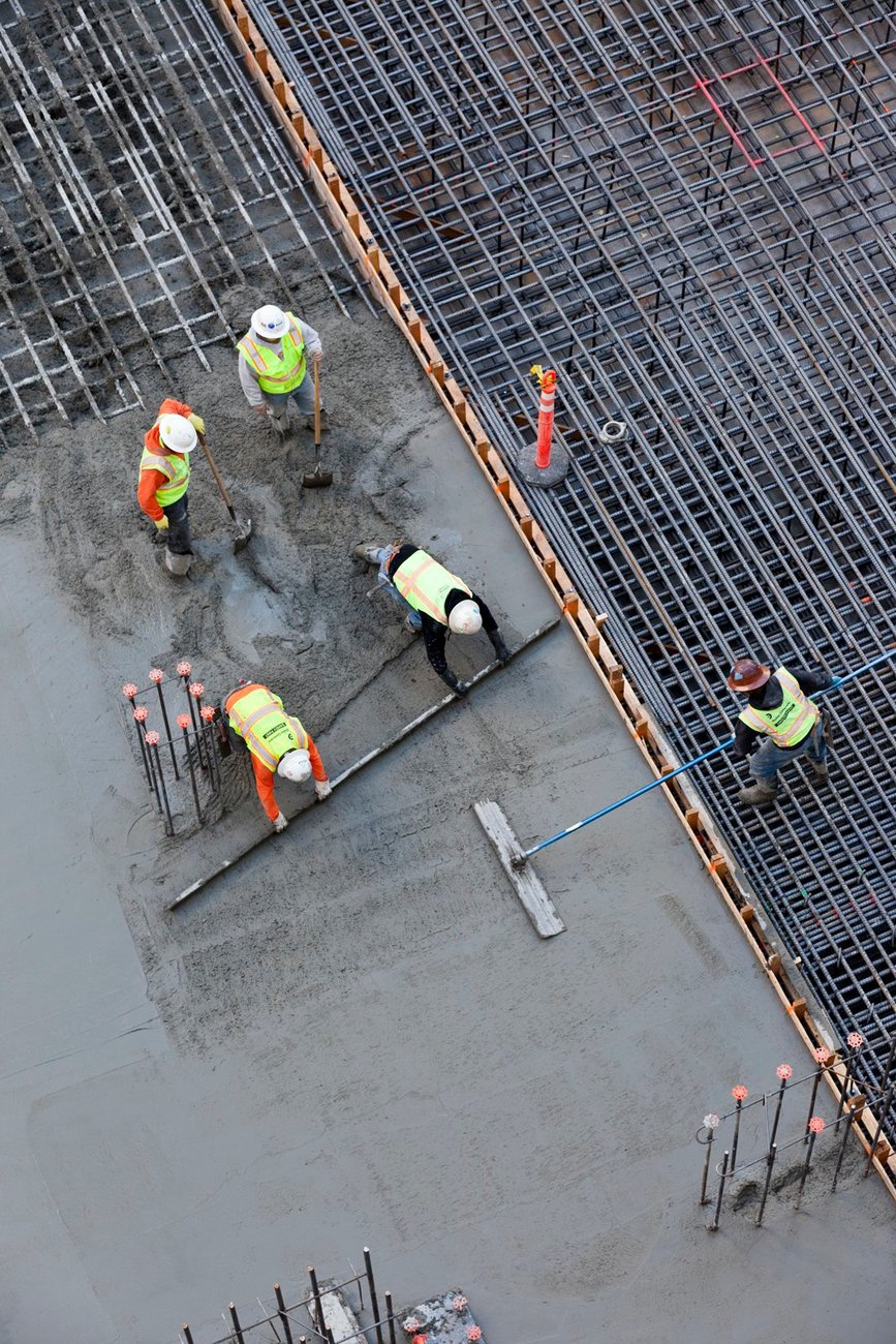 An overhead shot shows five construction workers laying a concrete foundation