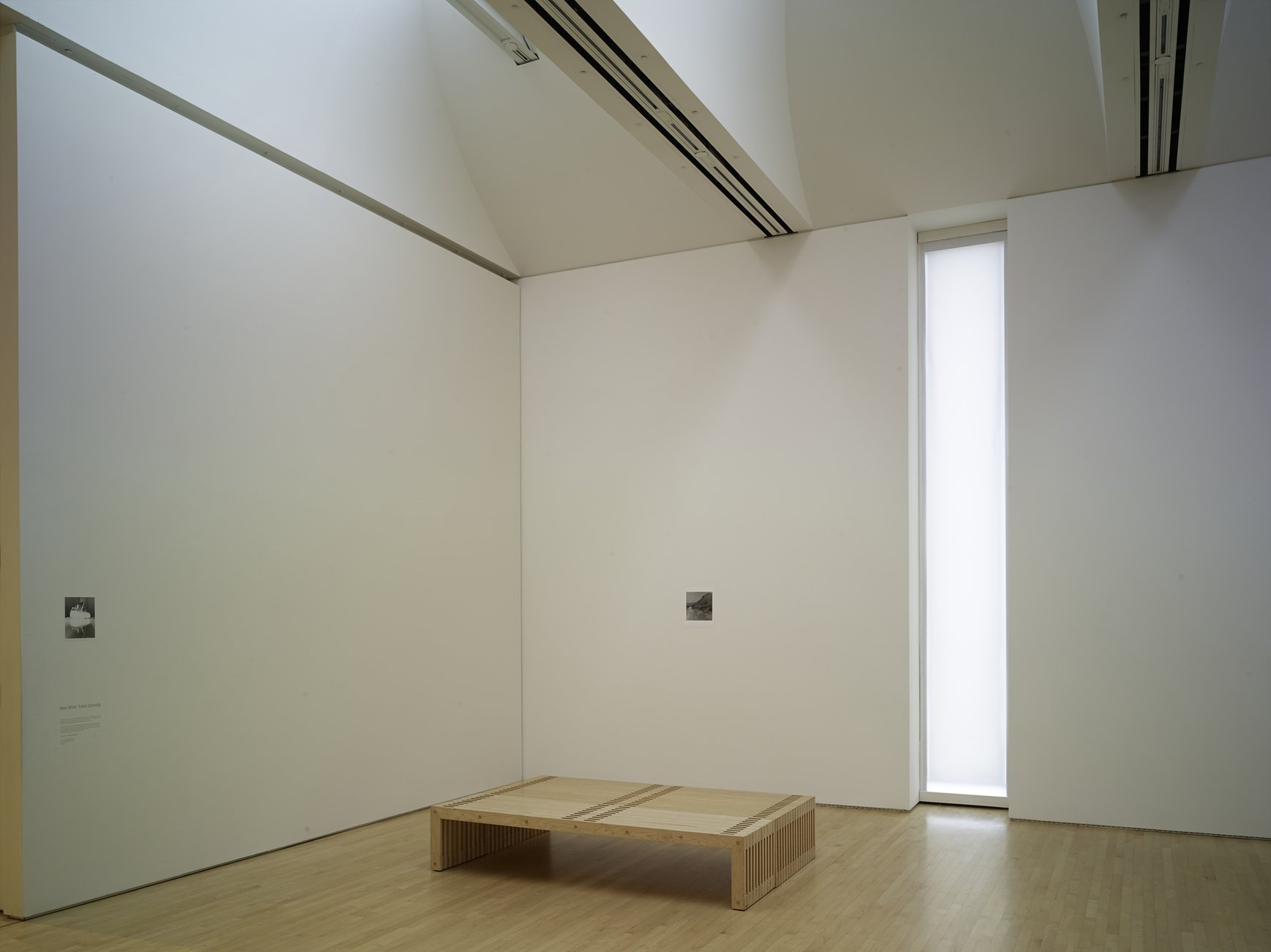 A room with two small photographs and a long glowing window.