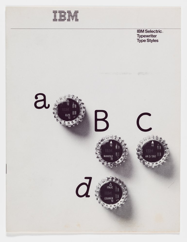 Antique typeballs sit on a paper next to letters