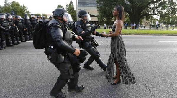 An African American woman stands serenely as riot police rush toward her