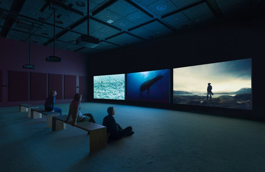 Three visitors watching a three channel video in a dark screening room