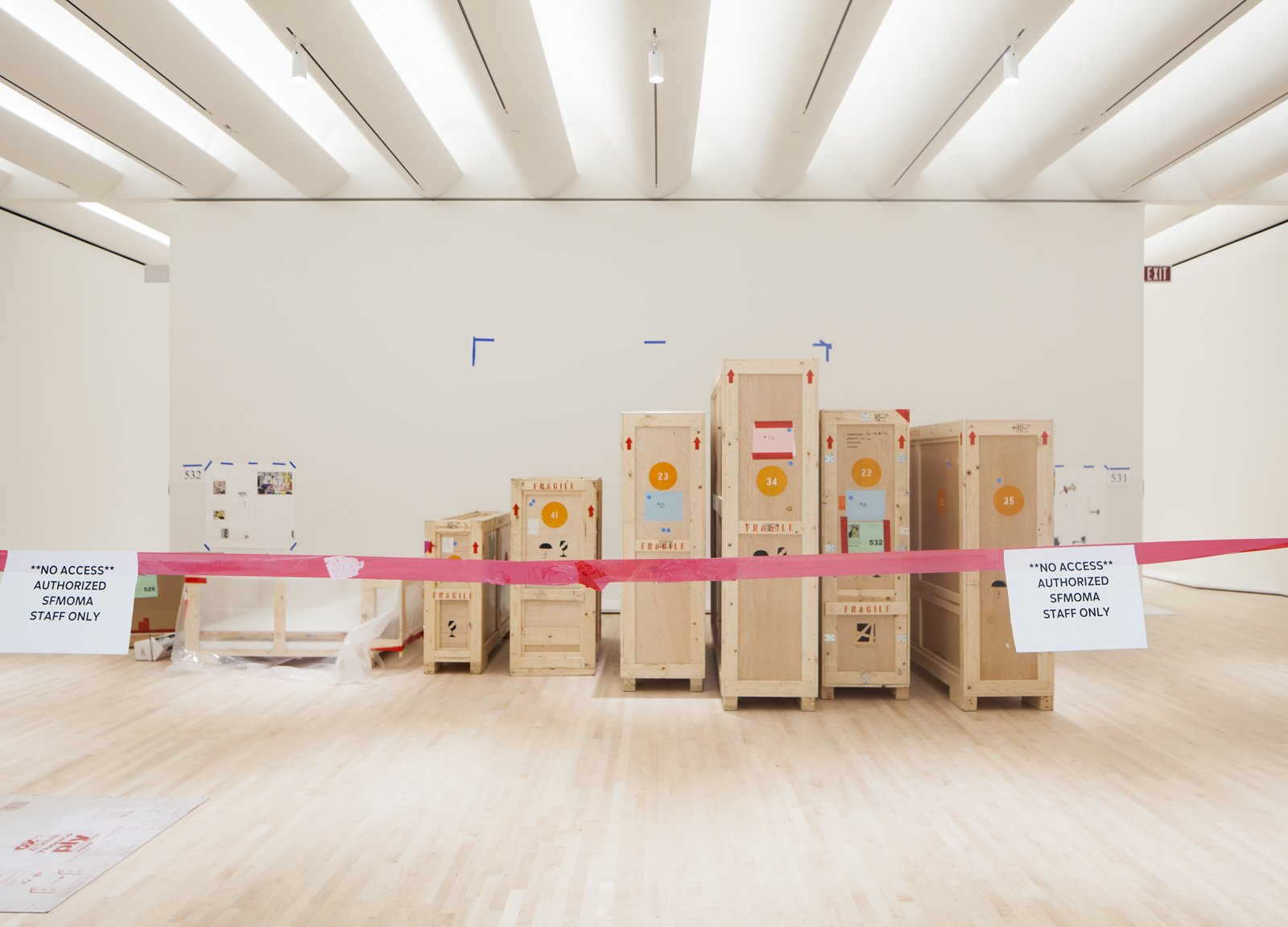 Crates sit behind a red rope in an empty gallery