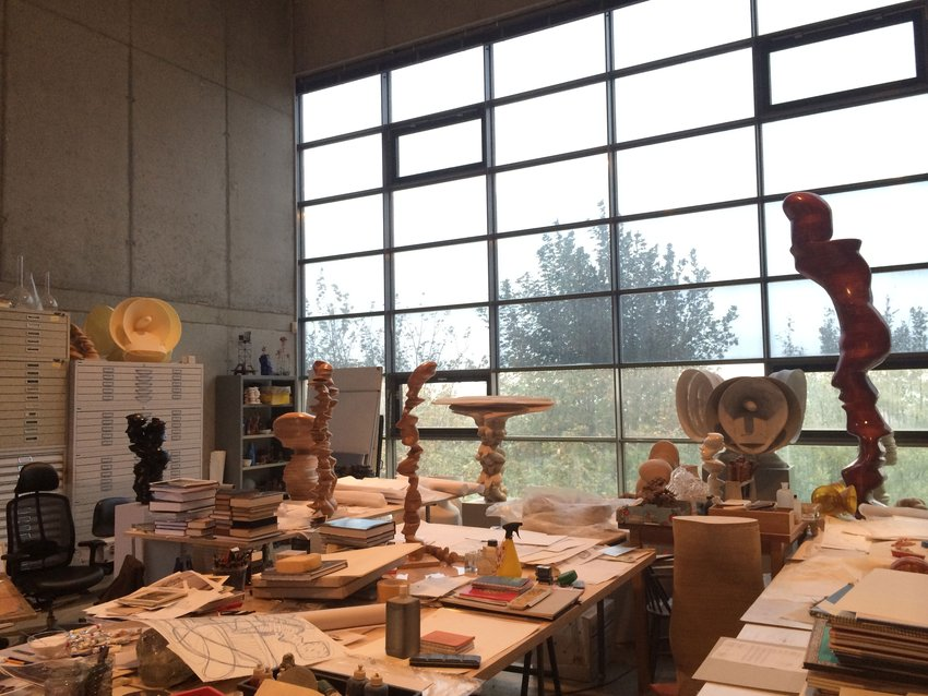 An artist studio table filled with art objects including papers, masks, against a rainy window