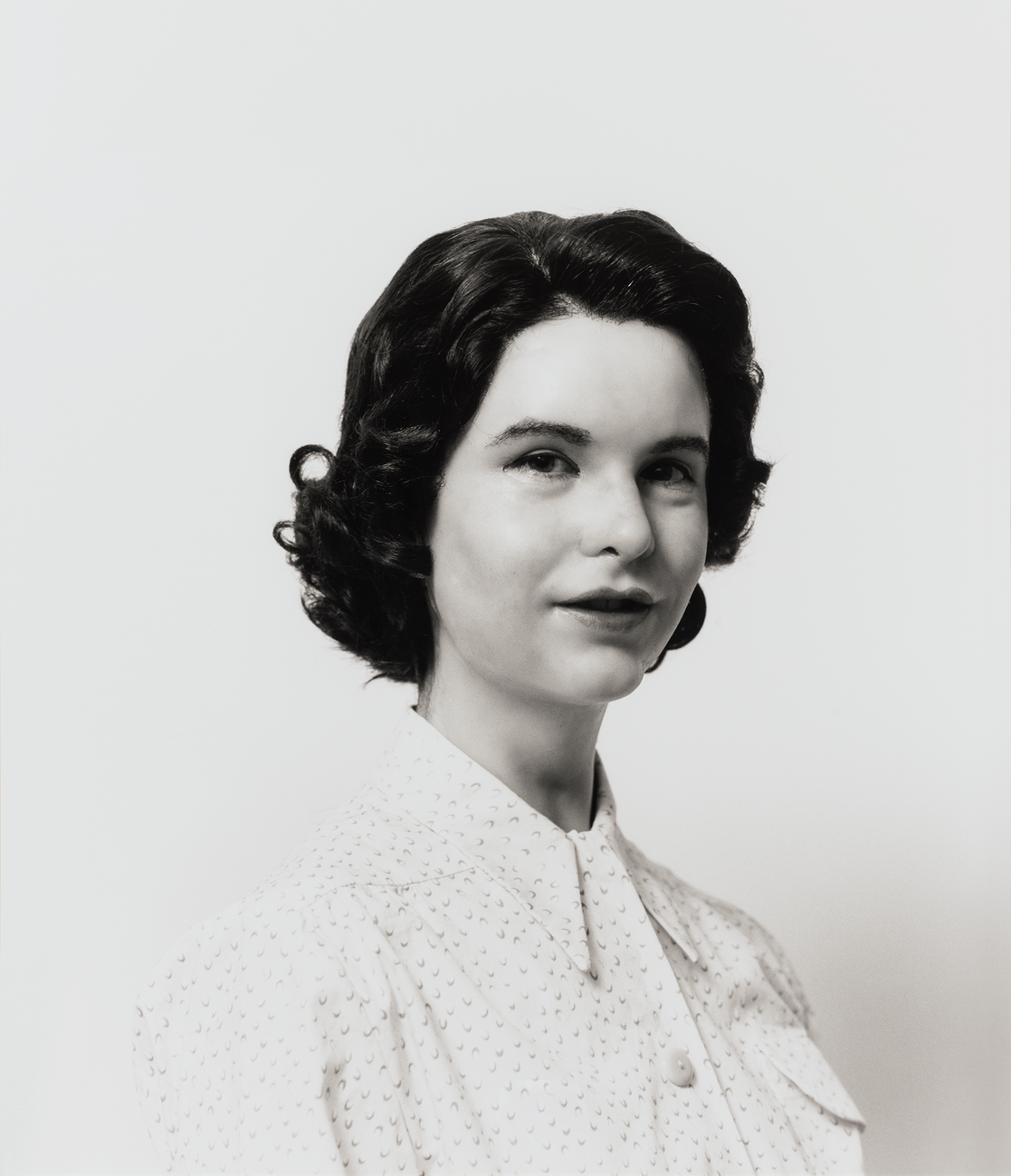 An uncanny black and white photograph of a white woman with 1950's style hair and blouse