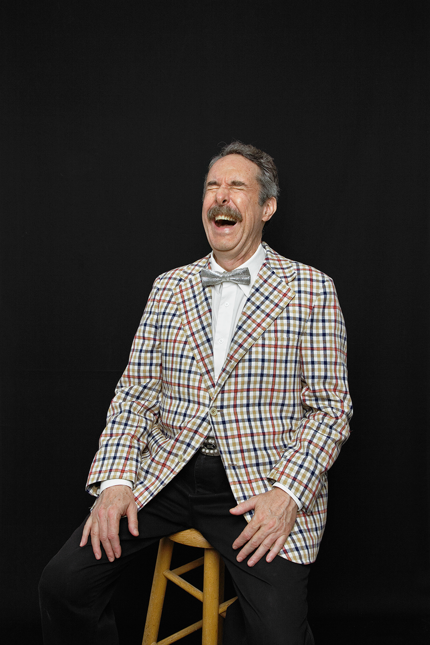A man with salt and pepper hair, a mustache, silver bowtie and plaid jacket sits on a stool and laughs with his eyes closed
