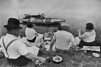 Cartier-Bresson, four people sitting on riverbed with boat