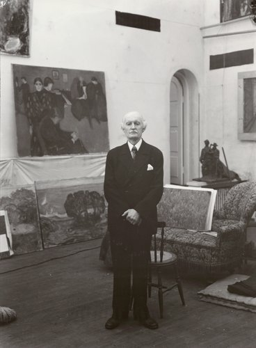 Black and white portrait of an elderly Caucasian man wearing a suit surrounded by paintings, Edvard Munch