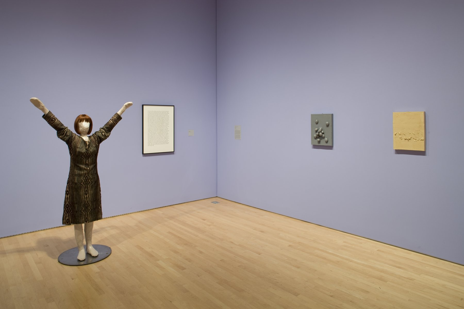 A sculpture of a woman with her hands raised in the air next to a framed block of text and two wall-hanging sculptures