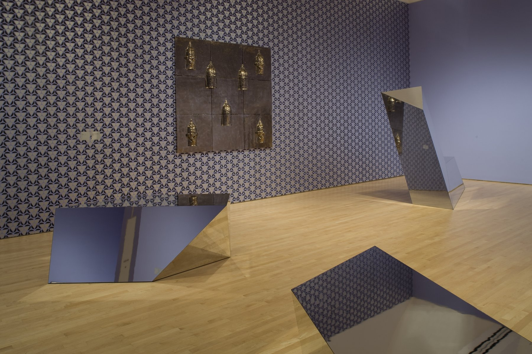 Three reflective geometric sculptures and a wall-hanging sculptures in a room with patterned wallpaper