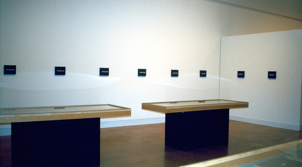 A row of small black blocks featuring white lettering hanging in a gallery