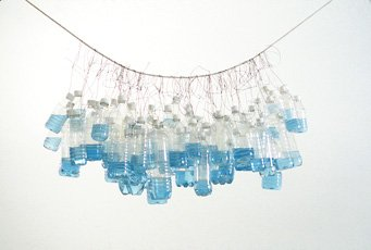 water bottles filled with blue liquid hanging from wire