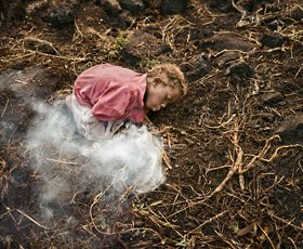 photo of young girl making fire on muddy ground