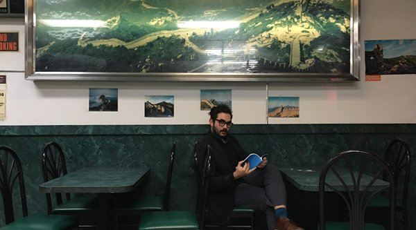Photograph of artist Arash Fayez sitting in a restaurant