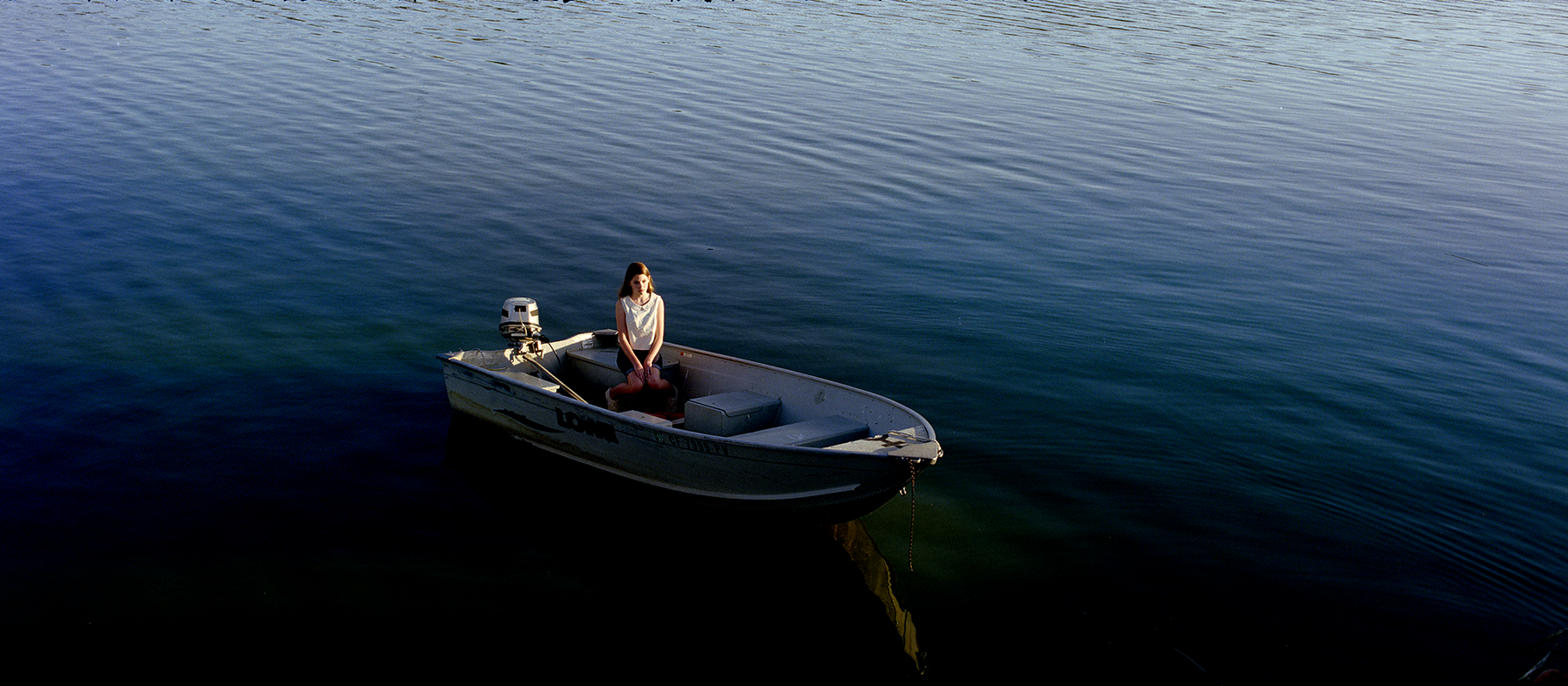 A sitting girl in a motor boat surrounded by blue water