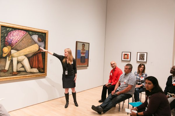 A woman points at a painting in front of a group of adults