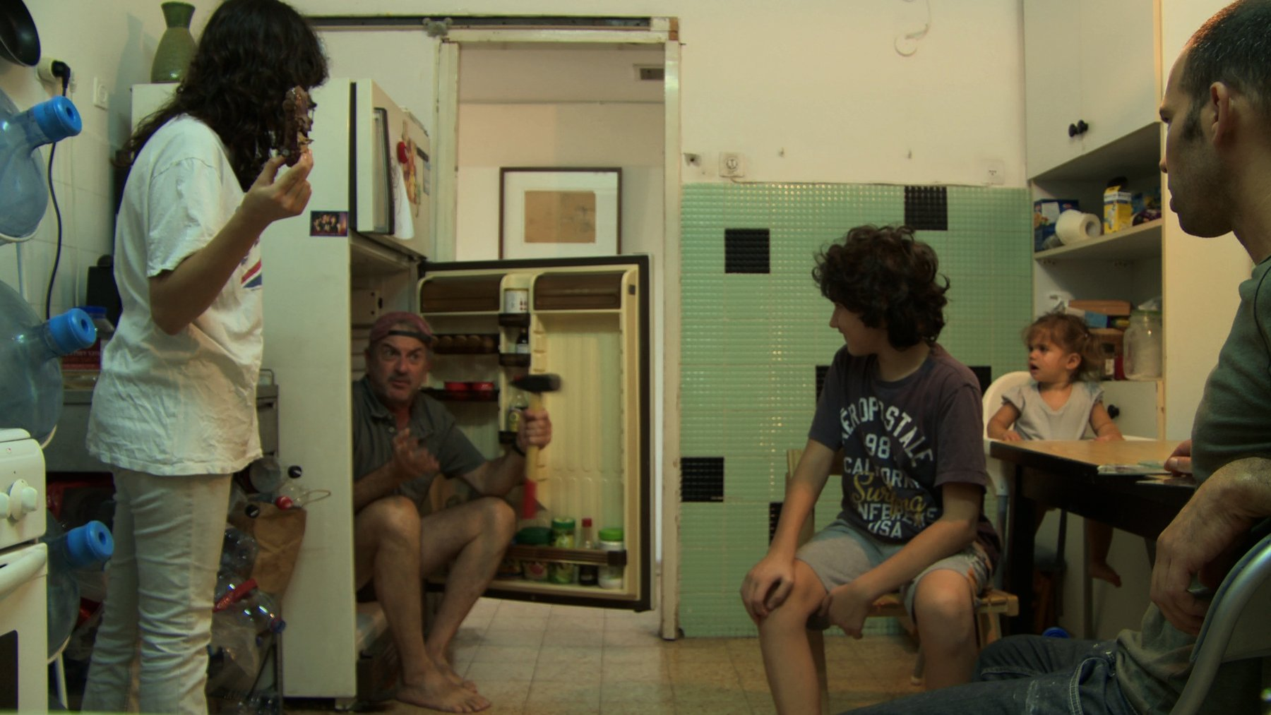 A middle-aged Caucasian man sits in an open refrigerator in a small kitchen surrounded by other adults and children, Ben Ner Soundtracks