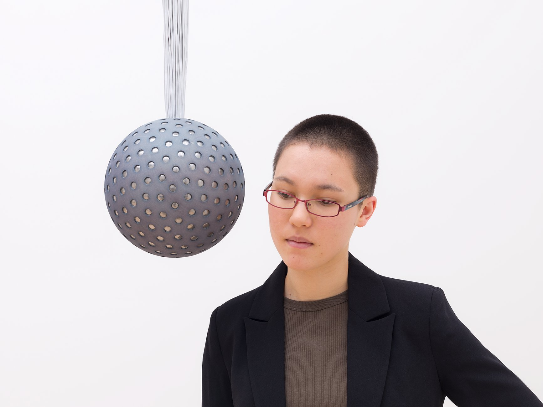 A woman wearing glasses with a shaved head leans into listen to a sphere suspended from the ceiling, Lozano-Hemmer, Soundtracks
