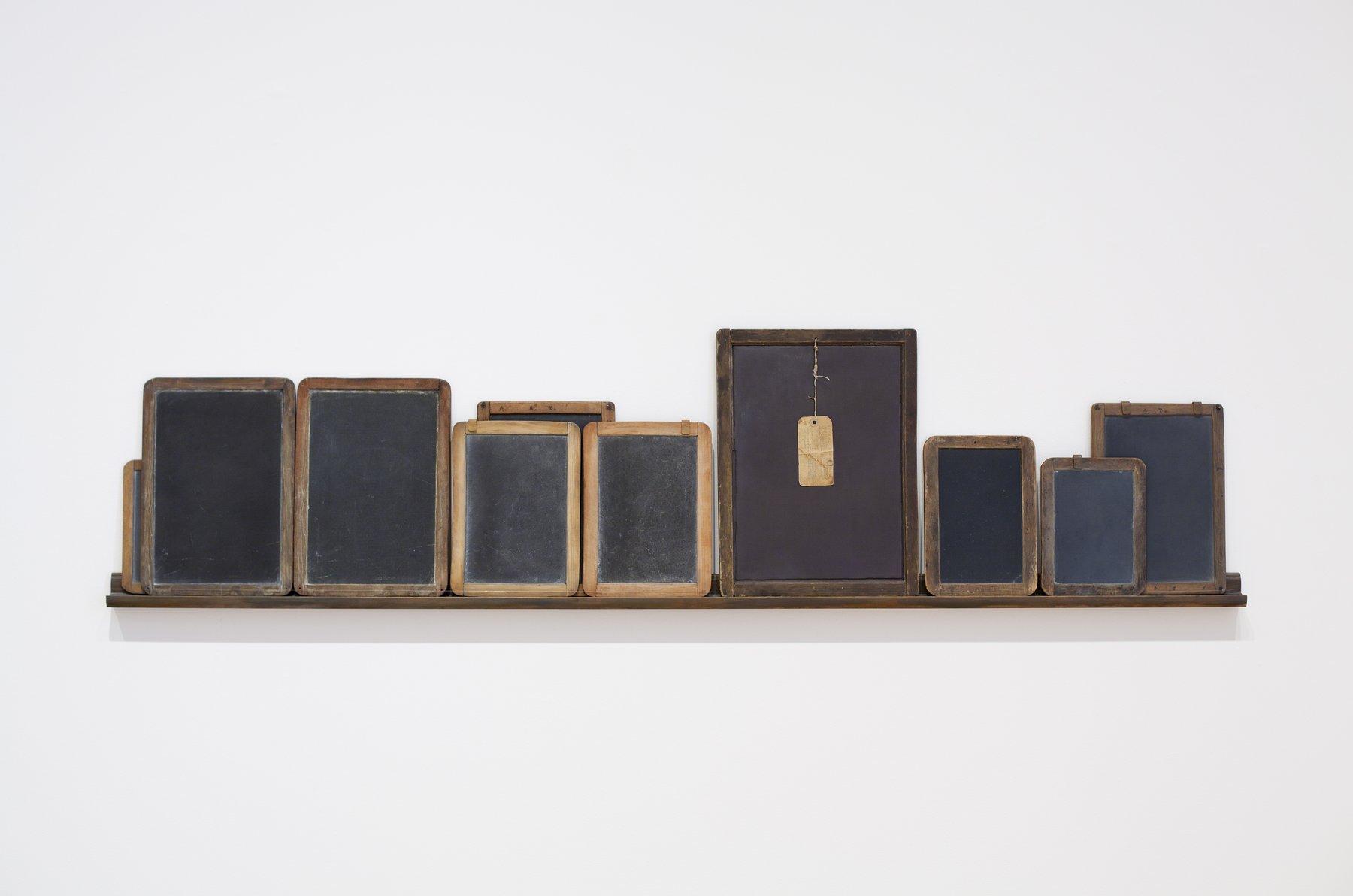 several rectangular wooden objects on a shelf, Vija Celmins