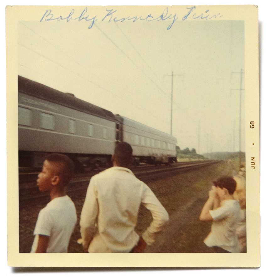 A faded square photograph of a group of black and white children and adolescents, seen from behind and in profile, watching a large train pass by from the train tracks