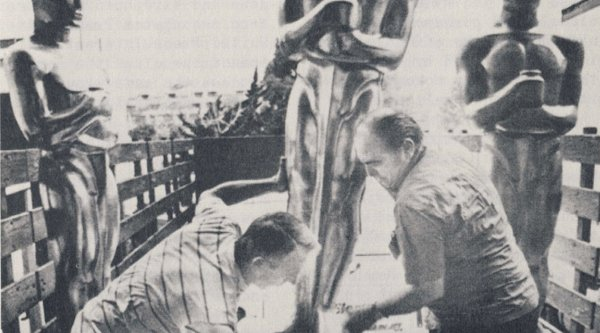 A black and white photograph depicting two men lifting life-size Oscar statues