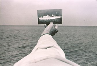 Josephson, hand holding photo of boat in front of ocean