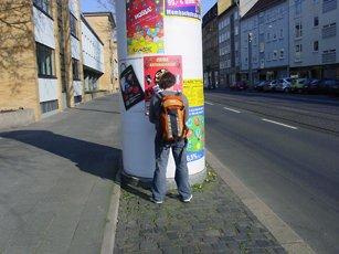 Ben Kinmont taping flyers to pillar