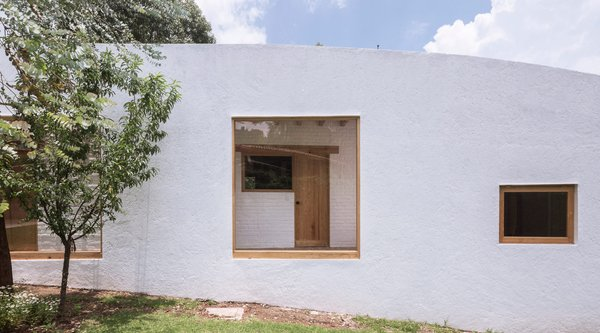 white stucco structure with window on grassy slope