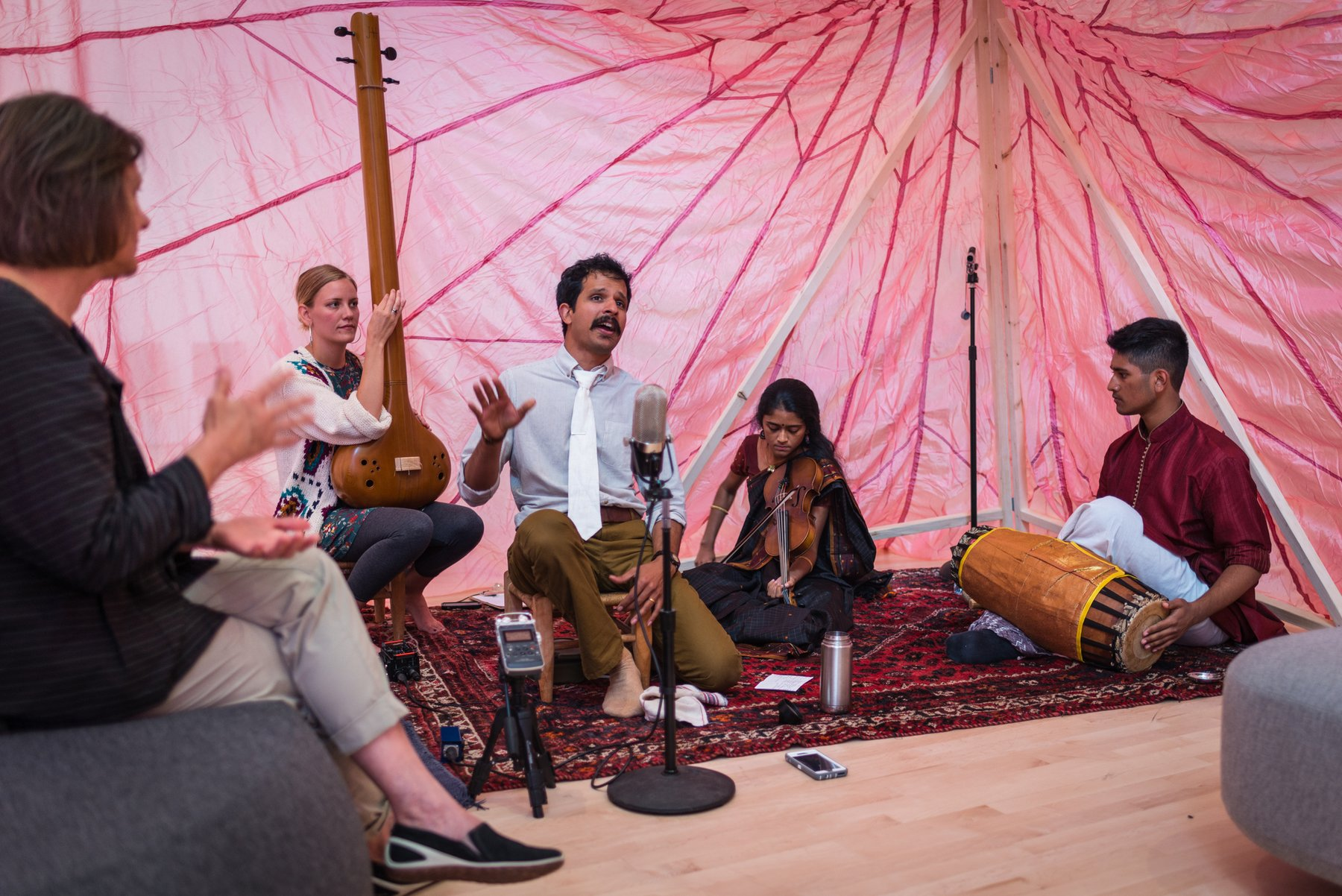 Musicians seated on a carpet with a pink fabric backdrop playing sitar, percussion and singing