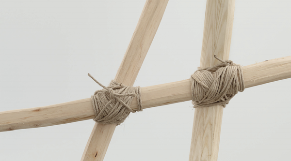 Three wooden sticks bound together with twine, close-up view of a Martin Puryear work