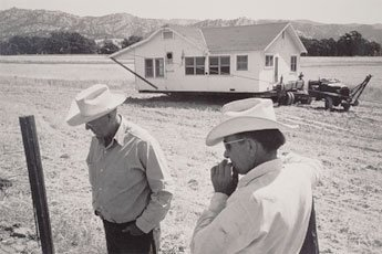 two men in cowbow hats on farm with house in back