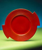 red ceramic plate on green table