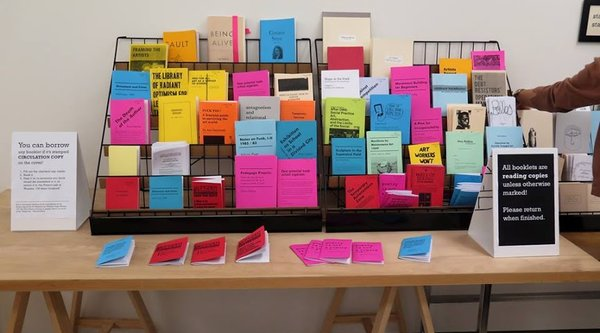 A color photograph of a wrack containing brightly colored pamphlets, Public Knowledge
