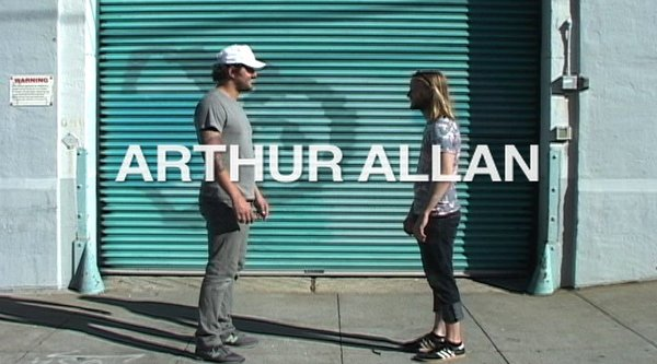 "Two men stand facing each other in front of a corrugated metal door with white text reading ""Arthur Allan"" overlaid"