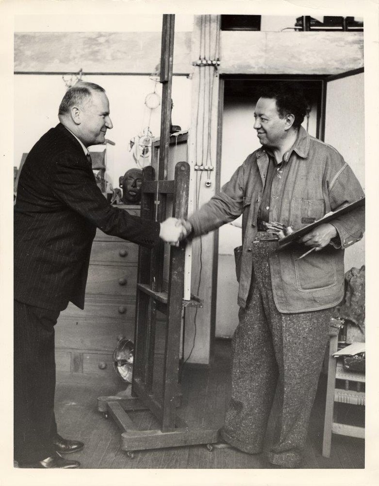 Photograph of Diego Rivera shaking hands with Timothy Pflueger