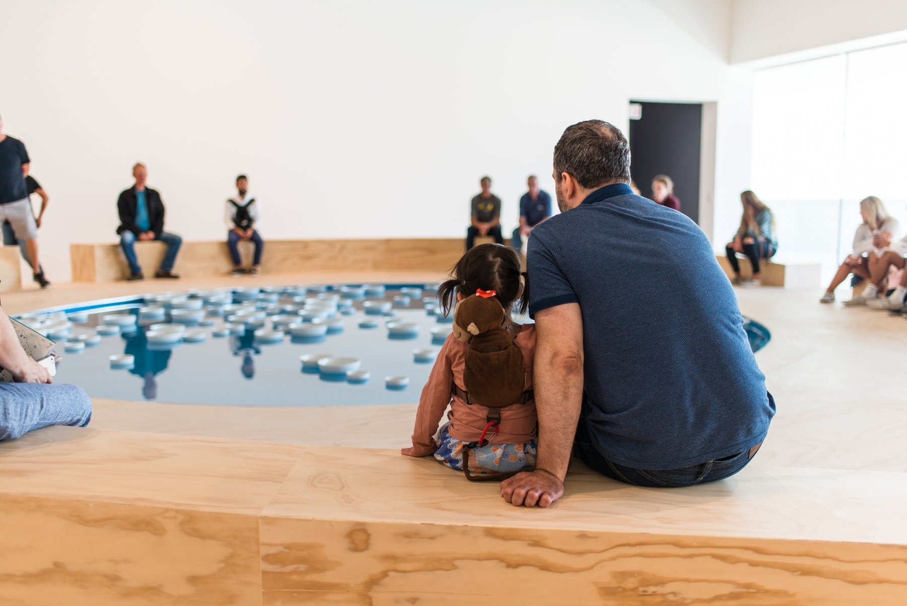 Color photograph of a father and son sitting on the edge of a blue pool of water filled with white bowls, Boursier-Mougenot, Soundtracks