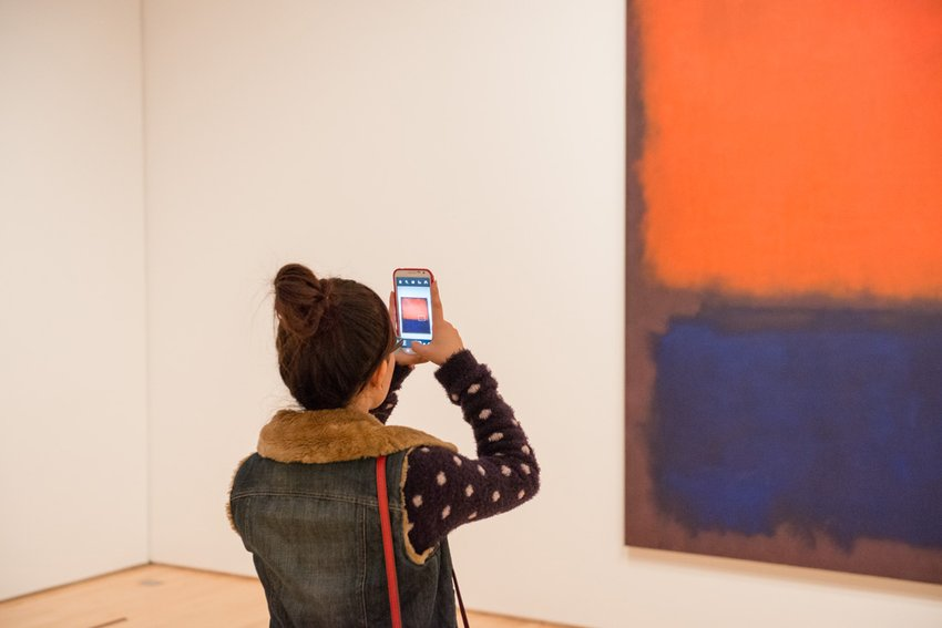 A woman in a bun holds her cell phone up to take a picture of an orange and blue painting